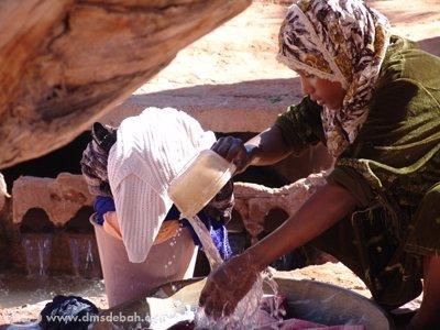 Une femme lavant son linge directement dans l'eau de la Foggara, avant répartition.